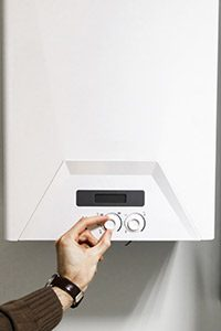 Person adjusting a tankless water heater setting