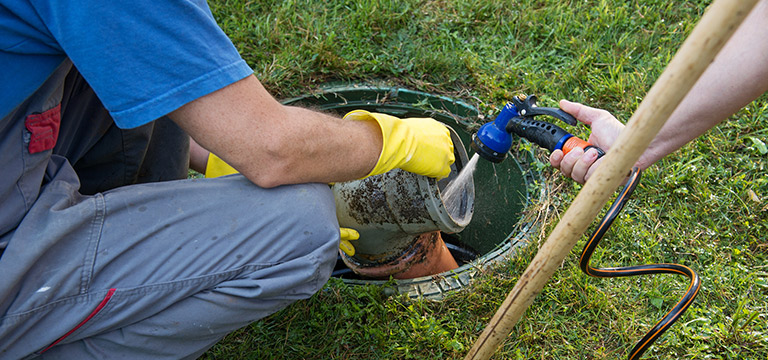 Image of a plumber inspecting a sewer.