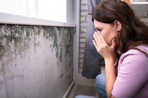 woman sees mold as a result of broken sewage pipes in her walls