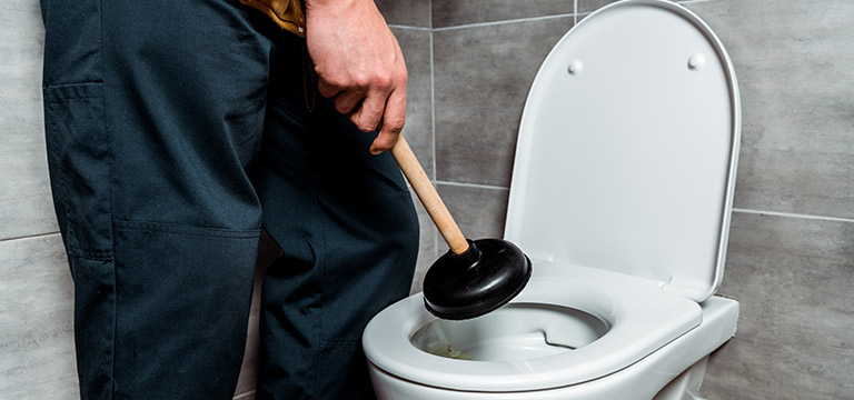 Plumber holing plunger over toilet with a drain clog
