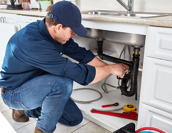 plumber discovering what causes gurgling pipes under kitchin sink