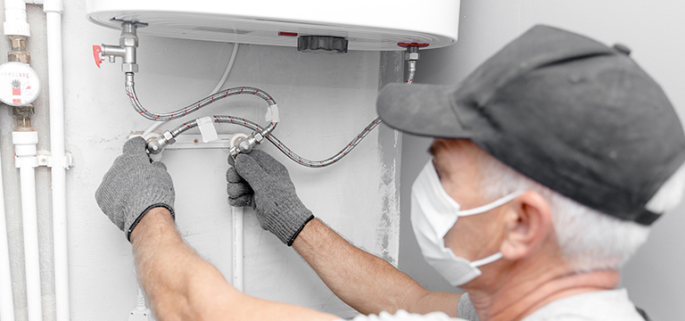 technician working on water heater replacement